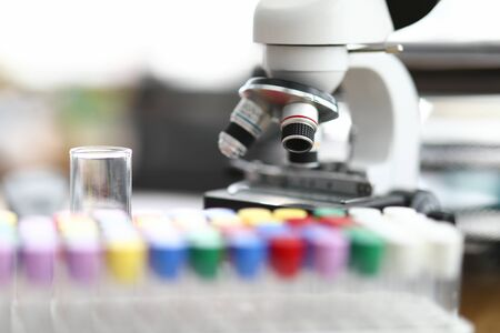 Close-up of modern microscope standing in laboratory office table. Glass flasks with colourful covers. Device to examine material in lab. Investigation and research sample concept