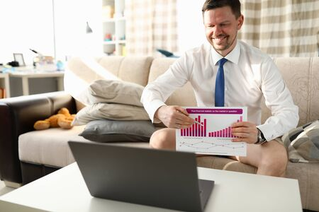 Manager without trousers sits home video conference. Manager sits at home in front laptop and shows report. Conducting training courses online. Informal appearance for remote work