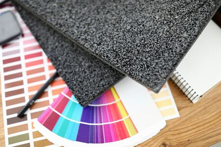 On table are carpet samples bright color palette. Check how selected colors are combined in real interiors designed by professional designers. Self-repair of the apartment. Color matching for interior