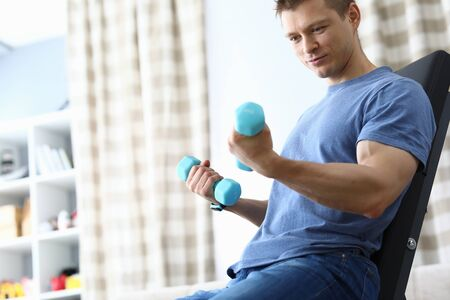Guy sitting home simulator and looking at dumbbells. Work out different muscle groups evenly. Muscle development and fat burning. Effective equipment for muscle development whole body