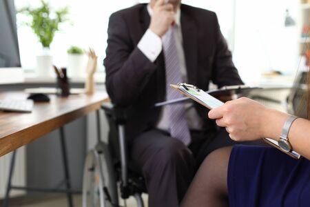 Il capo maschio sulla sedia a rotelle parla con la donna in ufficio. Prestigioso lavoro per persone con disabilità. L'uomo vestito si siede in sedia a rotelle. Tutela dei diritti dei lavoratori con disabilità