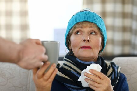 Elderly woman in scarf and hat sits on sofa home. Elderly lady takes cup tea. Weak immune system in old age. Woman in casual clothes sits at home on couch and holds in her hands cup that man gives her Stok Fotoğraf