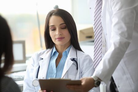 Young serious female person staring at list of prescription and listening to her colleague