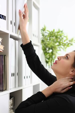 Concentrated office manager standing in semi position and putting folder with documents on the shelf