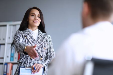Beautiful office woman holds out her hand to man. Well-developed intuition in workplace. Self-esteem and self-government in team employees. Male manager gets job in personnel department