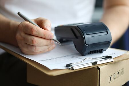 Man fills in home delivery mail document on box. Banking application. POS-terminal provides communication with bank. Man holds terminal app for payment and parcel. Courier brought package