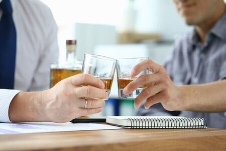 Men in suits drink alcohol in workplace at office. Communication business partners and solving important issues. Person is addicted to alcohol. Signing of an agreement on overcoming financial crisis