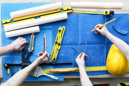 Men draftsmans on table draw construction project. An architect builds project on paper using measuring instruments. Builders calculate risks building. Joint work design department and builder