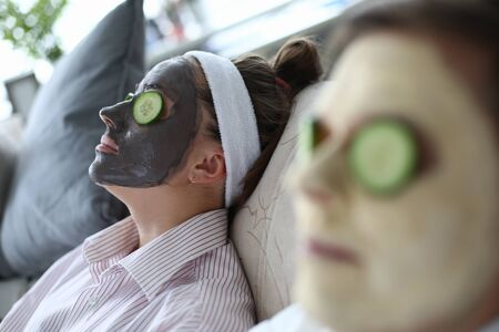 People are lying on couch with cosmetic mask faces. Man and woman lie with mask on faces cucumbers. Weekend relaxation. Matting masks for skin. Cucumbers on eyes to moisturize eyelids