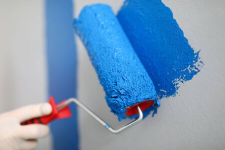 Hand holds roller and wire on wall with blue paint. Low roller performance. Convenient and versatile tool for painting walls. Tools with which best lay paint on surface. DIY repair in apartment