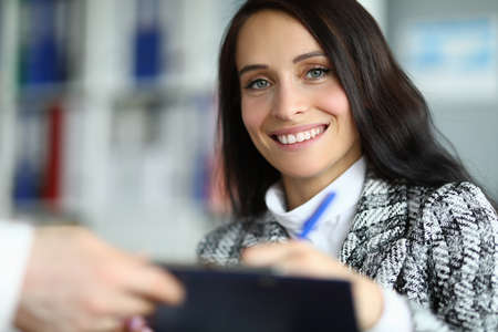 Close-up of cheerful pretty young woman smiling on camera. Lovely brunette lady signing document in company office. Good deal and success. Business and woman boss concept Banco de Imagens