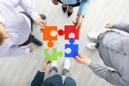 Group businees people hold color element puzzle top view background closeup. Each fulfills its task division of labor concept