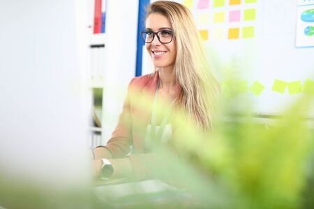 Portrait of cheerful blonde woman sitting in personal office. Stylish young female wearing black glasses. Green plant in room. Smart qualified company worker. Business concept