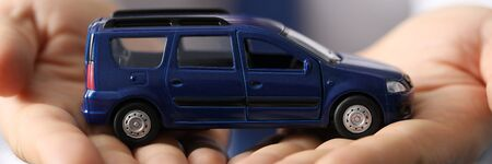 Closeup, man in shirt holds blue toy minivan car. Favorable car insurance. Inspection and diagnostics transport vehicles. International passenger transportation. Car sale from passenger compartment Reklamní fotografie