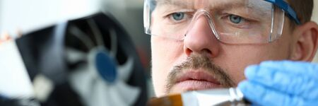 Close-up man goggles mends mechanical part device. Replacement thermal paste processor, lubrication active cooling system. Guy works at home during quarantine. Device repair in your apartment