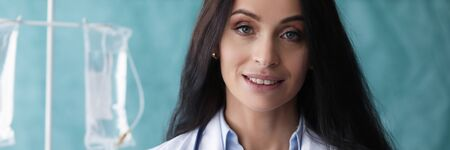 Beautiful woman doctor stand with folder smiling. Maintenance and restoration vital body functions in life-threatening conditions. Conservative medical and surgical treatment diseases