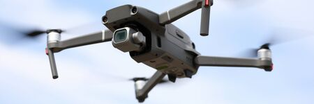 Close-up of digital camera on drone with remote control. Modern copter flying in sky. Shooting propeller option. Technology and innovation concept