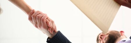 View from below of man and male shaking hands as hello sign of future collaboration prospects closeup