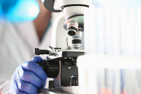 Close up of male researcher in sterile gloves looking at biological samples under microscope