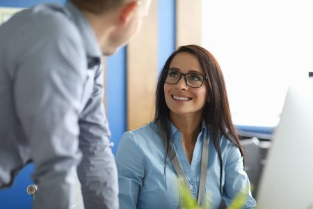 Portrait of smiling businesswoman looking at man with happiness and calmness. Happy businesslady speaking with colleague about profitable bargain. Business and company concept