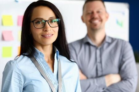 Portrait of happy businesswoman looking at camera with gladness and calmness. Smiling businesslady and colleague having break. Company and business concept
