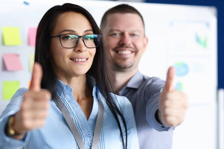 Portrait of smiling businesswoman and businessman looking at camera with gladness and calmness. Employees showing thumbs up. Company and business concept Standard-Bild