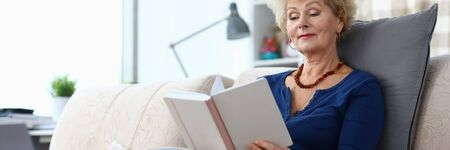 Elderly woman sits on sofa at home and reads book. Woman indulges in memories. View old photo albums and recall past times. Learning instructions for using laptop. Positive emotions from good memories Stock Photo
