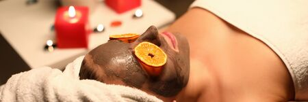 Girl lies in salon with clay mask on her face. After procedure skin face will look more radiant, youthful and renewed. Visible facial wrinkles are quickly smoothed out. Express facial skin care