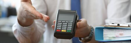 Man holds his hand wireless terminal for payment. Bank employee offers to install a wireless terminal for business. Providing customers with more convenient way to make settlements Stockfoto