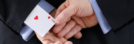 Close up man suit holds ace card behind his back. Identification exposure targets. Mastery methods influence, secrecy influence, preservation illusion. Goal achievement and selfish motives