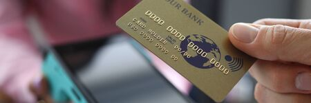 Man holds credit card with PayPass technology. Overdraft debit card. Making transfers. Portable terminal delivered to house. Electronic services bank. Payment for services through online banking