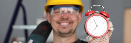 Male builder helmet laughing showing alarm clock. Performance repair work within specified period. Noisy work with drilling holes concrete. Happy builder finished work. Deadlines and employee safety