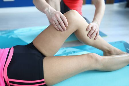 Close-up of mans hands massaging womans leg. Female laying on blue mat in sportswear. Fit body. Yoga class for adults. Sport and active healthy lifestyle concept