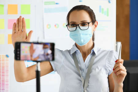 Business woman in protective mask say hallo on smartphone camera portrait. Business online education concept