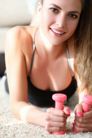 Cropped photo of happy pretty woman doing fitness exercise with dumbbells at home. Sport and health concept