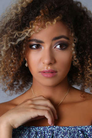 Close up of confused pretty Afro American woman with an afro hairstyle posing in studio against grey background Stockfoto
