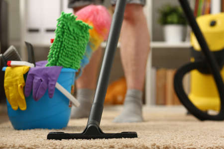 Cropped photo of man cleaning the carpet and using a bucket and rags in the living room