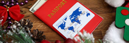 Close-up of red passports cover with banknotes in it. White and blue plastic credit card on top. Bright festive christmas decorations on wooden table. Holiday concept 免版税图像