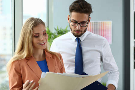 Waist up of smiling pretty lady standing near her male colleague while holding documents in the office
