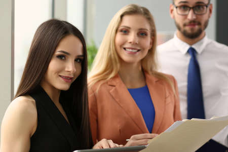 Smiling pretty lady holding digital tablet and standing near her employees. Business concept