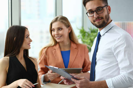 Happy bearded man holding document and talking with his two female colleagues at workplace Standard-Bild