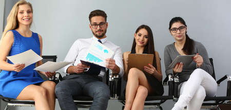 Happy young man and three women waiting for an interview and holding questionnaires in hands