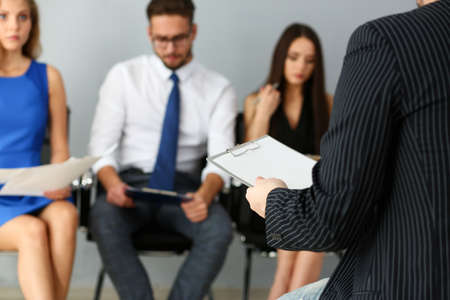 Cropped photo of male manager holding a questionnaire and waiting for an applicant for an interview Stockfoto