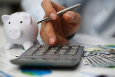 Close up of finance officer working at a table with documents and using a calculator while holding pen. Finance and analytics concept Standard-Bild