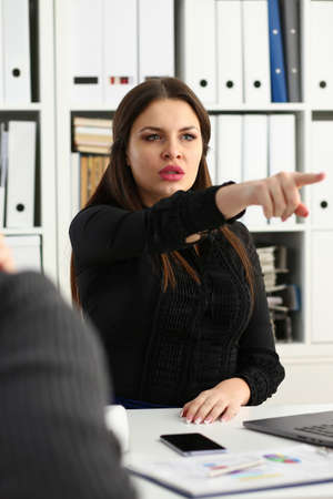 Sad female manager sitting at workplace while talking with subordinates during meeting in the office