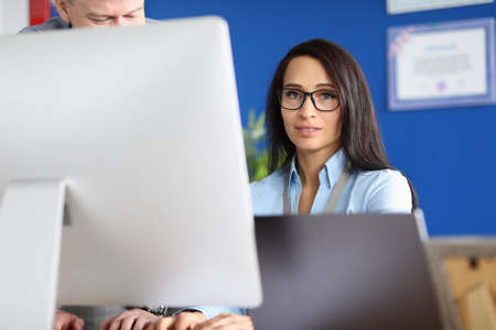 Indecisive young woman in glasses sits at computer. Training programs for continuing education of office staff concept