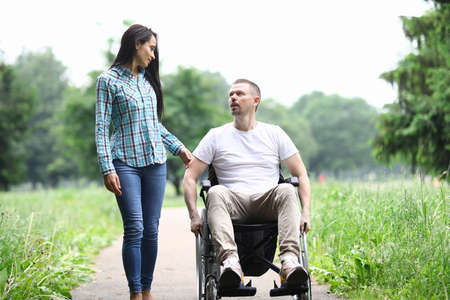 Woman and man in a wheelchair walk in park and talk. Walking in park with people with disabilities concept