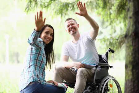 Woman and man in wheelchair happily wave. Mutual assistance and volunteering concept 免版税图像 - 151062532