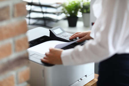 Woman in office prints documents on printer. Scanning documents at workplace concept