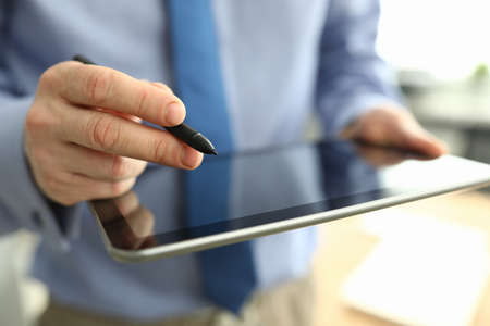 Man holds tablet and digitally signs. Small business development and support concept